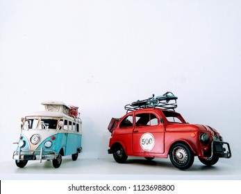 PHANG NGA, THAILAND - JUNE 23, 2018: Models of camper van & car are on white background, travel concept & space for text. VW Van is in blue and white and Beetle car is red, hipster & hippie style.