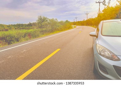 Phang-Nga, Thailand - 3 May 19 :  Closeup Front view of new Silver blue car parks on asphalt roadside  with  countryside street curved & tropical summer forest on clouds sky background in sunlight