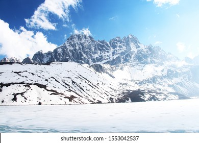 Pharilapche mountain rises above Gokyo lake covered with ice in Himalayas in Nepal near Gokyo village and Renjo La Pass. White clouds on a blue sky. Mountains in Sagarmatha national park.