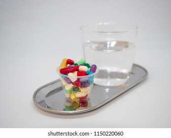 Pharmaceutical drugs and medicines in a measuring cup with a glass of water on a silver tray
