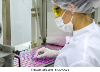 Pharmaceutical Production Line. An employee oversees the packaging of the medical pills. Pharmaceutical manufacturing technician wearing protective clothing.