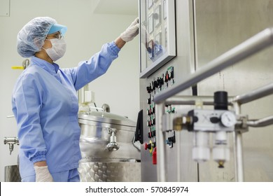 Pharmaceutical Technology . Female worker at pharmaceutical factory operating control panel of the pharmaceutical machine. Biomedical and pharmaceutical research.