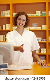 Pharmacist behind counter reaching out with her hand