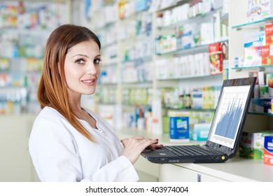 Pharmacist checking stock values on her laptop in the pharmacy near shelves