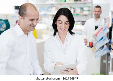 Pharmacist and customer. In the background we can see another pharmacist