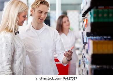Pharmacist And Customers At Pharmacy In Front Of Shelves With Pharmaceuticals.