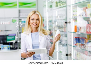 pharmacist with digital tablet and medication smiling at camera in drugstore