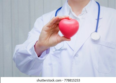 pharmacist or doctor with stethoscope around his neck and hand holding red heart in hospital, heart attack, pharmacy, laboratory research, science, chemical, health care and medical technology concept