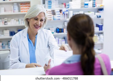 Pharmacist giving prescriptions of medicine to customer in pharmacy