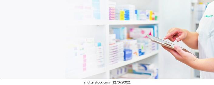 Pharmacist holding computer tablet Using for filling prescription in pharmacy drugstore.