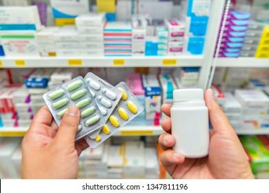 Pharmacist holding medicine pack and medicine bottle in pharmacy drugstore.