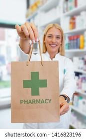 Apotheker, die eine Papiertüte mit einem grünen Pharmacy-Logo in einer Apotheke hält