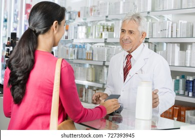 Pharmacist Looking At Female Making NFC Payment For Shampoo