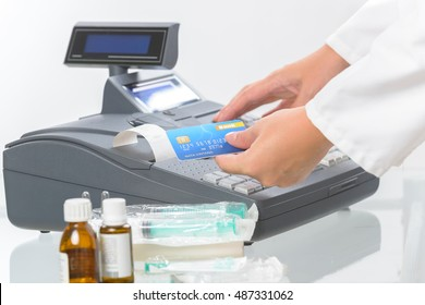 pharmacist or medical doctor holdnig credit card and using cash register at pharmacy or surgery