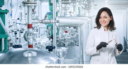 Pharmacist with medicine in a syringe against the background of pharmacological production. concept of the production of medicines during an epidemic covid-19