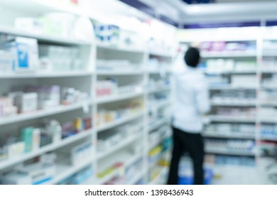 pharmacist picked up and check medicine in shelves in phamacy store on blur photo