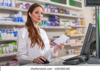 pharmacist with prescription at the cashier desk operating the computer. portrait of a young medic in pharmacy