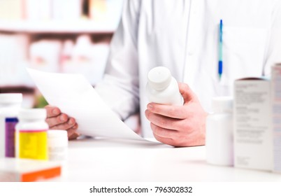 Pharmacist reading prescription with medicine and pill bottle in hand in pharmacy. Medical professional in drugstore counter. Clerk or druggist in drug store. Pharmaceutical retail business concept.