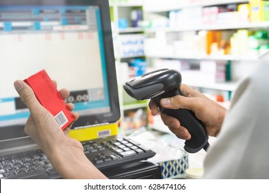 Pharmacist scanning price on a red medicine box with barcode reader in pharmacy store