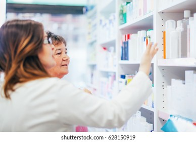 Pharmacist and senior costumer looking and searching for a medication on pharmacy shelf