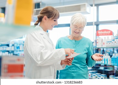 Pharmacist servicing senior customer in her pharmacy holding bottle with pills in her hand