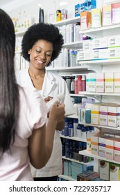 Pharmacist Showing Product To Customer In Pharmacy