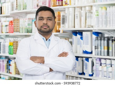 Pharmacist Standing Arms Crossed Against Shelves In Drugstore