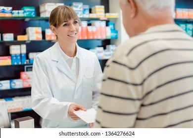 Pharmacist taking prescription slip from senior man standing in front of shelves