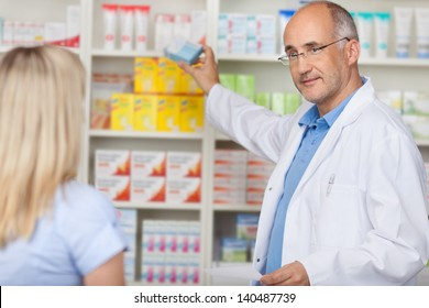 pharmacist talking to female client while taking medicine of the shelf