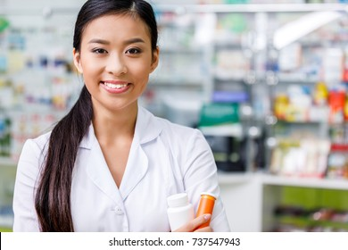 pharmacist in white coat holding containers with medication and smiling at camera