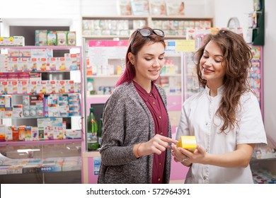Pharmacist woman inside a pharmacy showing a box to customer. Healthcare and medical business. Consultation of a professional druggist seller in store