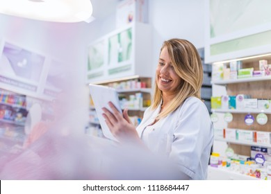 Pharmacist working with a tablet computer in the pharmacy holding it in her hand while reading information. Cheerful happy pharmacist chemist woman working in pharmacy drugstore with tablet computer