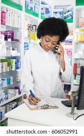 Pharmacist Writing On Clipboard While Using Cordless Phone