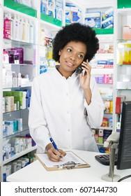 Pharmacist Writing On Clipboard While Using Telephone