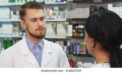 The pharmacist and young woman are in the pharmacy. The client talks about her complaints. The chemist listens to her very carefully. He shakes his head knowingly