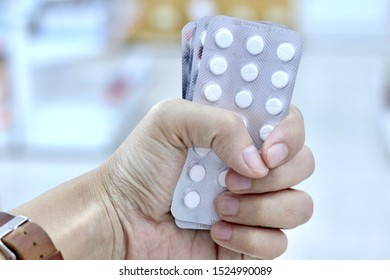 The pharmacist's hand is holding white compress tablets in blister pack is medicine that is  dispensing by pharmacist.