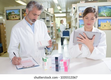 pharmacists holding tablet in hands while doing inventory