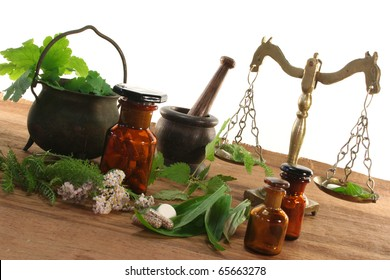 Pharmacists scale with mortar, old pot, apothecary jar and fresh herbs