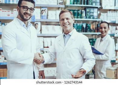Pharmacists is Working. Two Men Handshaking with Each Other. Persons is Smiling. Woman Writing Information about Medicine. People Wearing Special Medical Uniform. Persons Located in Pharmacy.
