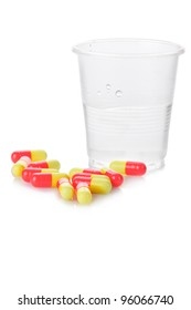 Pharmacy. Antibiotic pills and plastic glass of water on white background