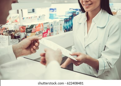 At the pharmacy. Beautiful young female pharmacist is listening to a client while working at the cash desk, man is giving a prescription