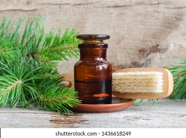 Pharmacy bottle with essential pine oil (extract, tincture, infusion) and wooden foot and body brush. Old wooden background. Aromatherapy, spa and herbal medicine concept. Copy space.