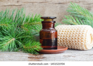 Pharmacy bottle with essential pine oil (extract, tincture, infusion). Old wooden background. Aromatherapy, spa and herbal medicine concept. Copy space.