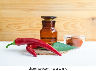 Pharmacy bottle with  red chili pepper extract (tincture, infusion, oil) and fresh chili pepper pods. Baldness, alopecia natural remedy and pain relief. Copy space.