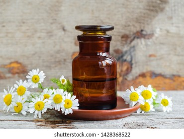 Pharmacy bottle with roman chamomile essential oil (extract, tincture, infusion). Old wooden background. Aromatherapy, spa and herbal medicine concept. Copy space.