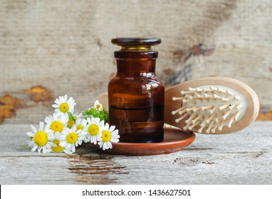 Pharmacy bottle with roman chamomile essential oil (extract, tincture, infusion) and wooden hair brush. Old wooden background. Aromatherapy, natural hair care, spa, herbal medicine concept. Copy space
