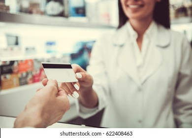 At the pharmacy. Cropped image of young female pharmacist taking a credit card from a client while working at the cash desk
