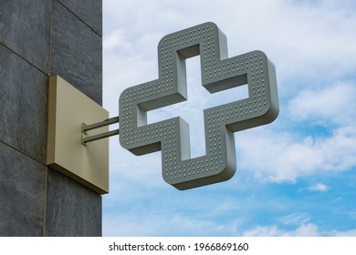 Pharmacy cross in the background against the sky with clouds