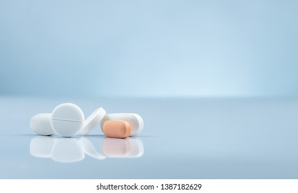 Pharmacy drugstore product. Pile of orange and white tablets pill on gradient background. Different size and shape tablets pills. Pharmaceutical industry. Medicine in hospital. Retail drug market.