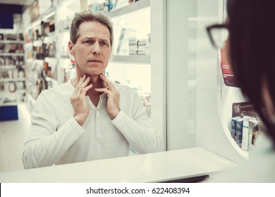 At the pharmacy. Handsome client is talking to a beautiful female pharmacist at the cash desk and showing that he has a sore throat